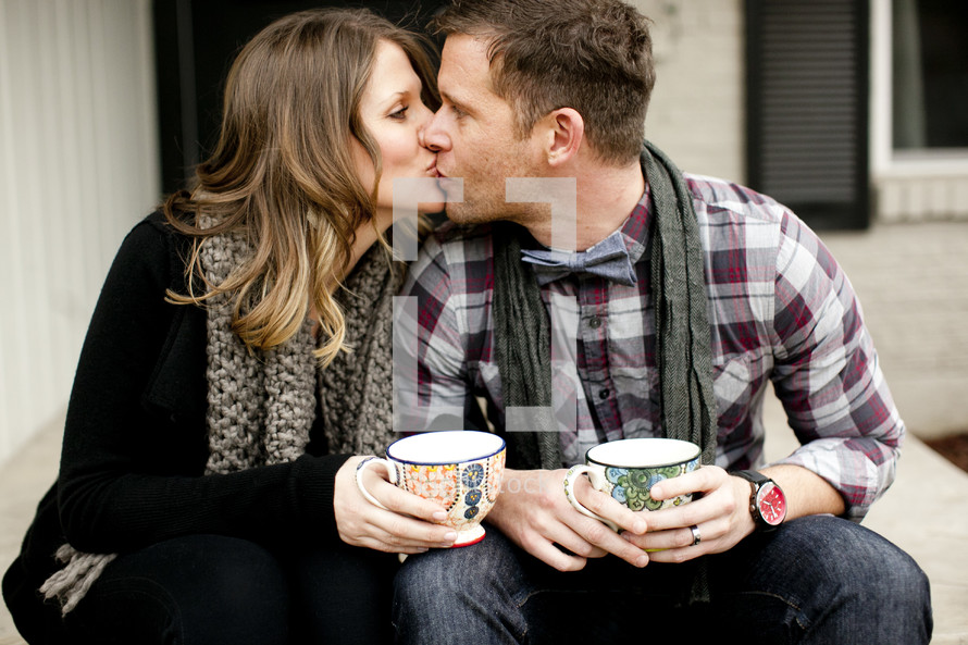 couple kissing holdig mugs of coffee