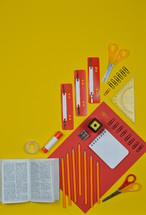 office supplies on red and yellow and Bible