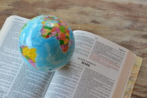 a globe resting at the bible open to the page, Matthew 28.