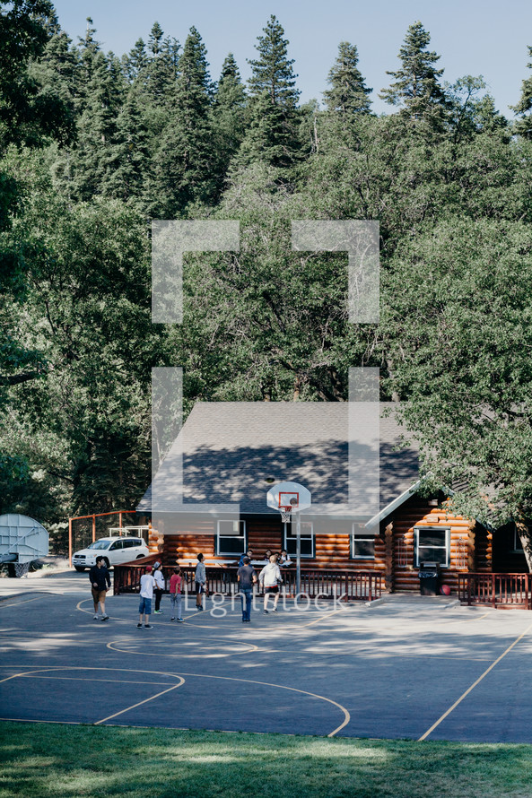 youth playing basketball in front of a log cabin
