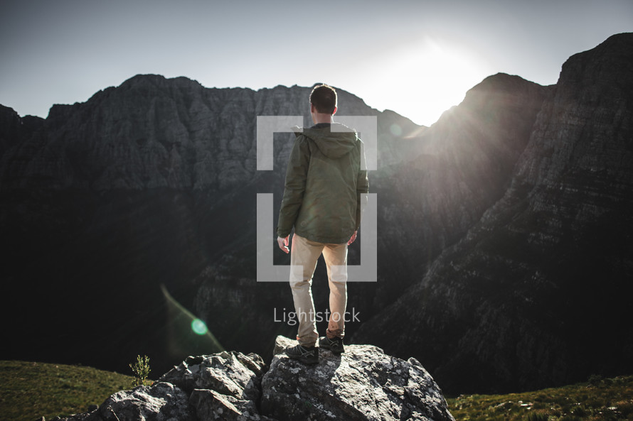 a man standing on a rock looking out at the view on a mountaintop