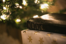 gifts and a Bible under a Christmas tree