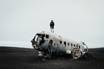 a man standing on the ruins of an airplane crash site