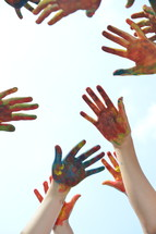 finger paint on the hands of kids with raised hands