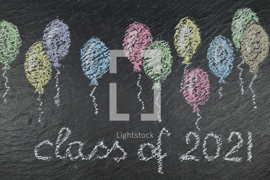 chalk on slate with balloons and the words: class of 2021