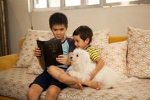 brothers sitting on a couch reading a Bible with their dog