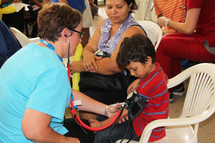 children receiving medical care from a doctor at a missions clinic