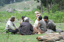 men gathering in a circle having a meeting outdoors.