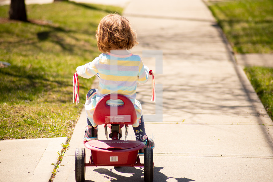 A toddler riding a bicycle in the sun on a summer day.