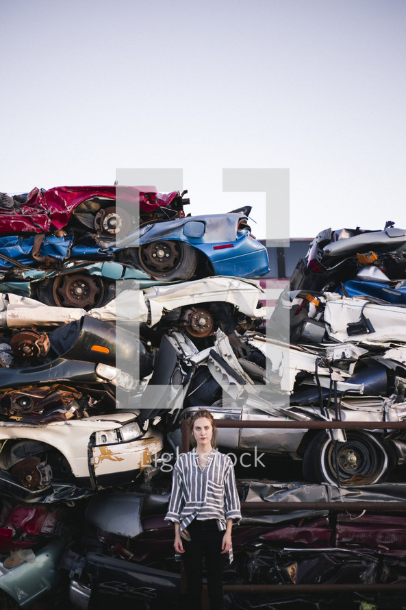 a woman in a scrap metal junk yard standing by crushed cars