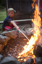 A young boy poking a campfire with a stick.