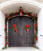 garland and Christmas wreaths on wooden doors
