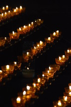 many lit candles in a dark church. 