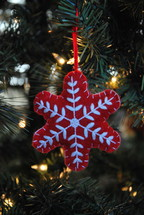 red snowflake ornament on a Christmas tree