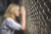 a woman clinging to a chain link fence