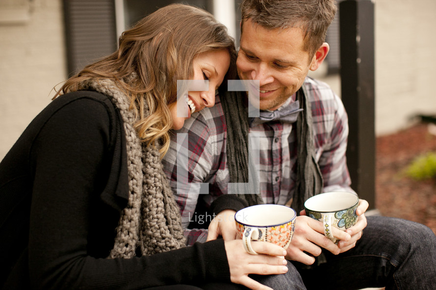 couple holding coffee mugs outdoors sitting on a step