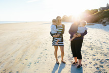 mother and grandmother holding children on a beach