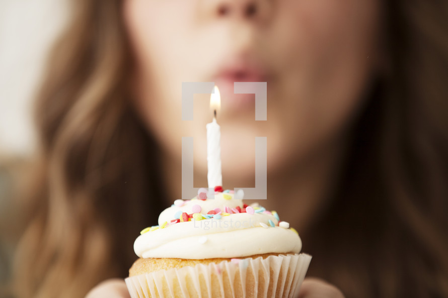 a woman blowing out a candle on a cupcake