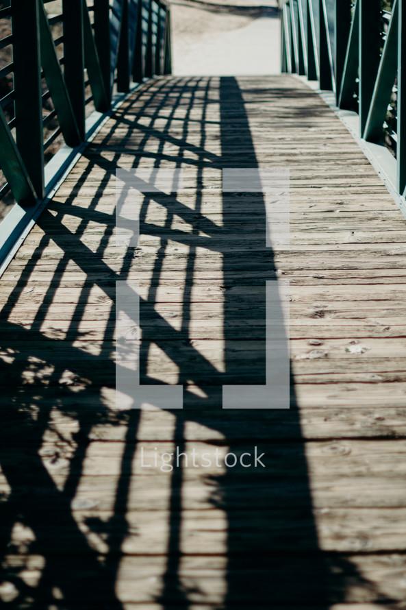 rail shadows on a wood bridge