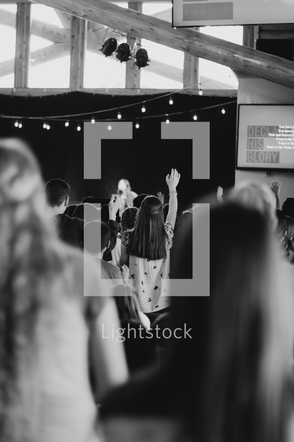 girl with arm raised during a worship service