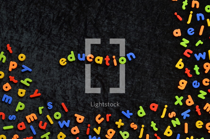 the word EDUCATION written with colorful magnetic letters on black ground
