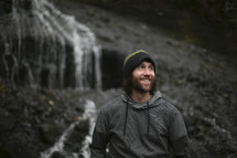 a man with a beard standing in front of a waterfall