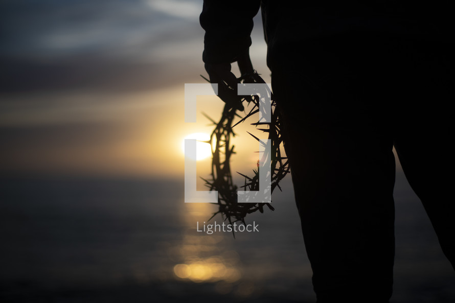 a man holding a crown of thorns on a shore at sunset