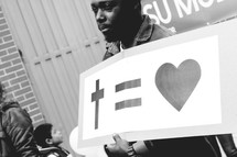 A man holding a sign cross = heart
