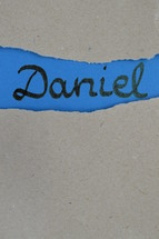 book Daniel - torn open kraft paper over blue paper with the name of the prophetic book Daniel