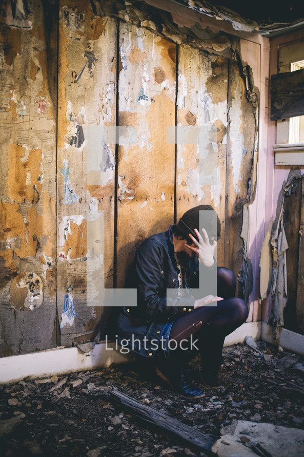 A woman sits sits in an abandoned house with her head in her hands.