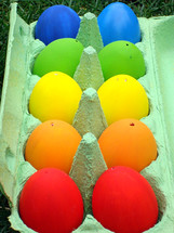 10 multicolored eggs in an egg carton.