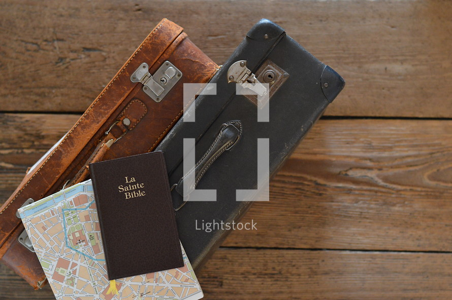 two old weathered suitcases with a map of Paris and a french bible on a rustic wooden floor