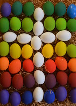 White cross between colorfully painted Easter eggs.