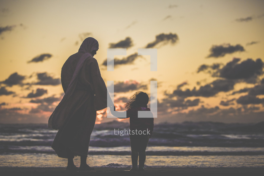 Jesus holding hands with a little girl standing on a beach at sunset