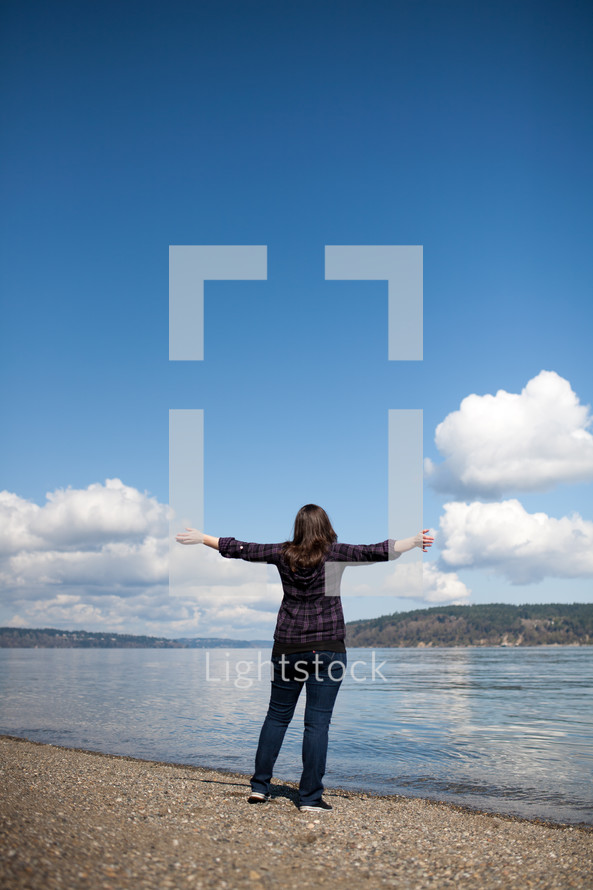 Woman at water's egde with arms extened giving praise to God.