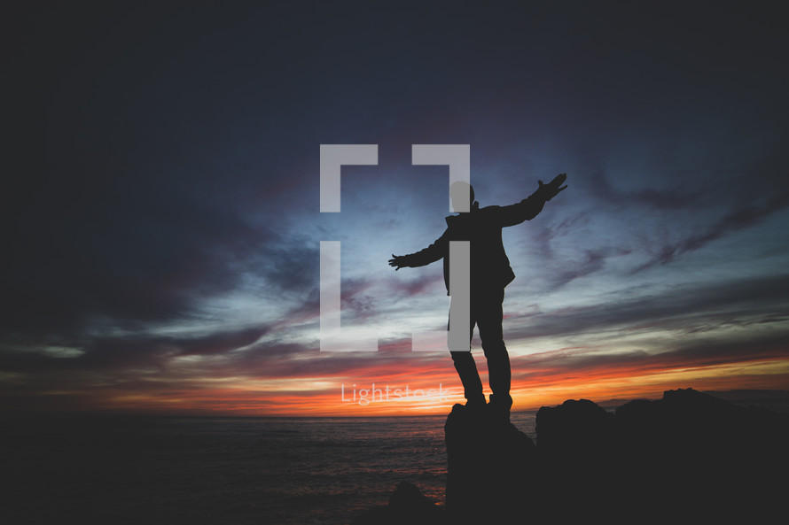 a man standing with outstretched arms on a shore at sunset