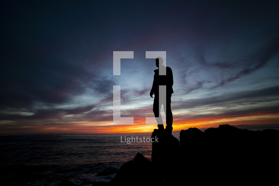 man standing on a rock along a shore at sunset