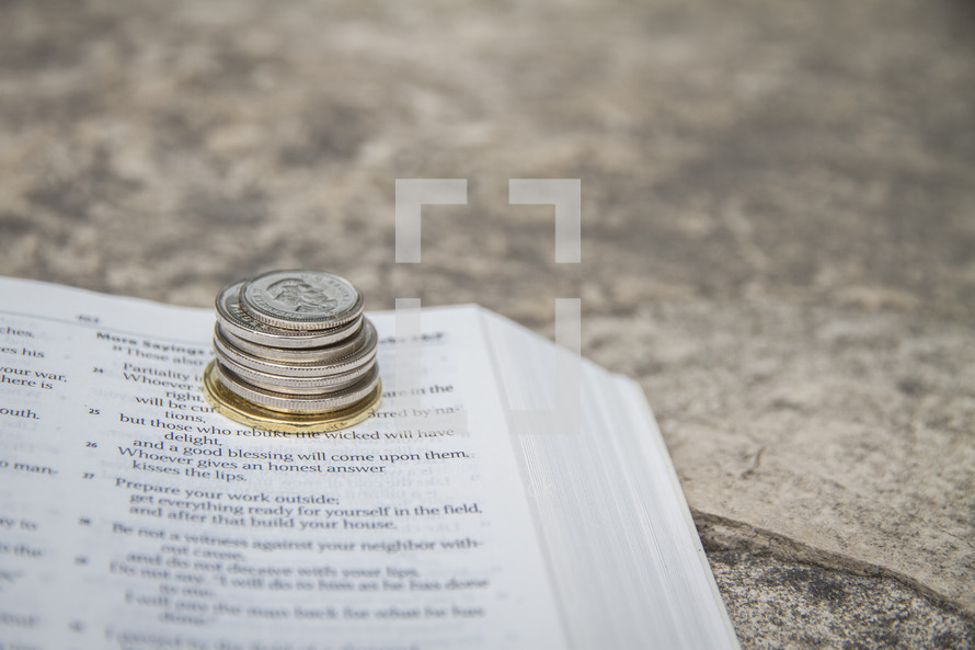 Canadian money on a Bible with a rock background