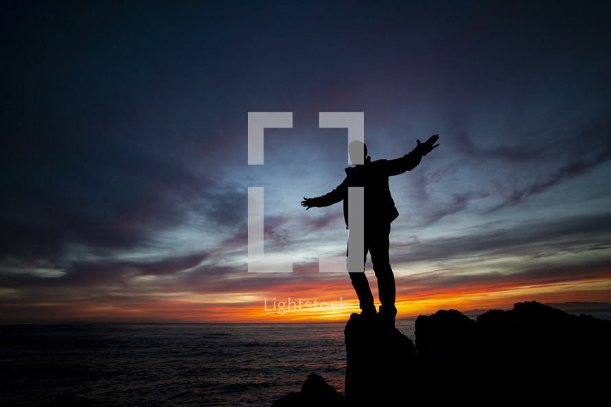a man with outstretched arms standing on a rock by the ocean at sunset