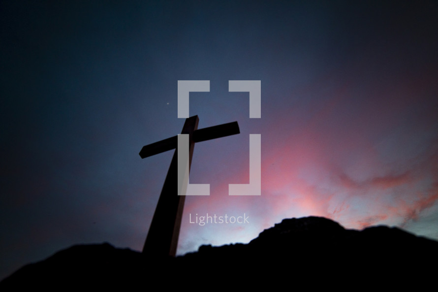 a silhouette of a cross at sunset