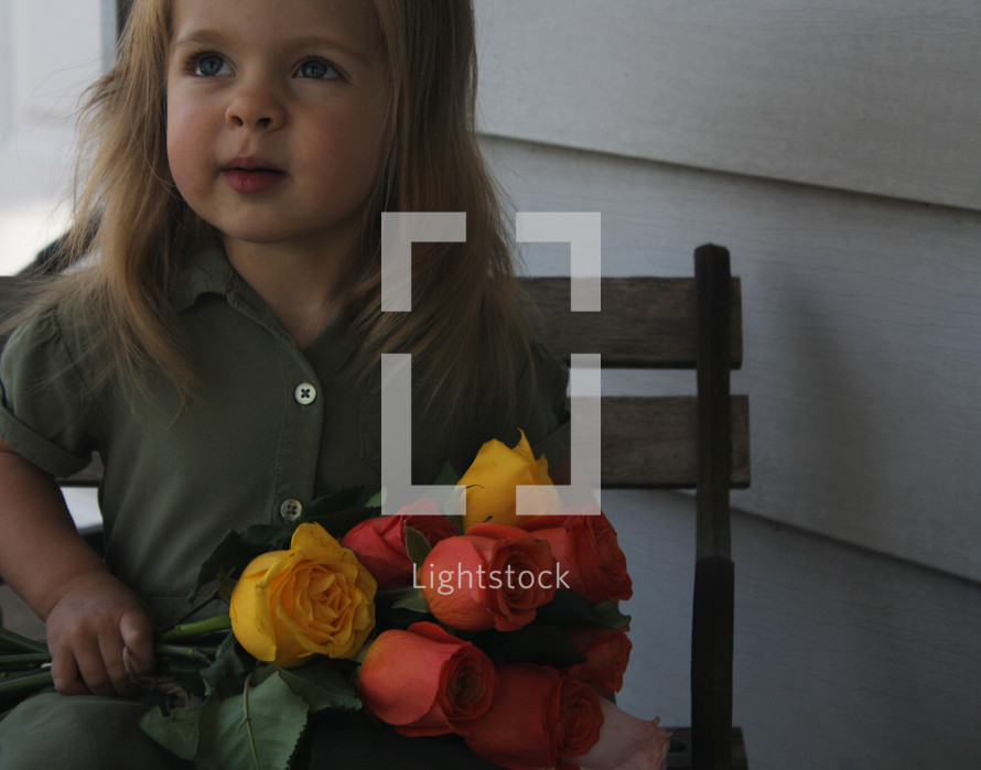 a little girl holding a bouquet of tulips for mom