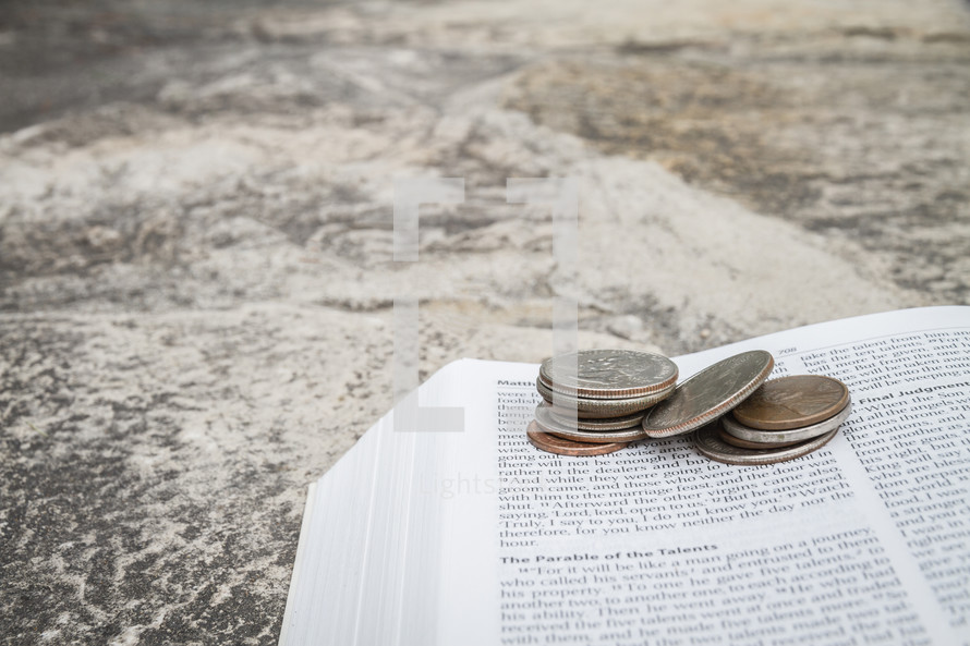 Money on an open Bible with a rock background