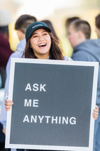 "A laughing woman holding a sign reading, ""Ask Me Anything."""