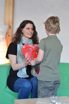 a boy giving his mother a heart