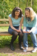 women praying together on a park bench