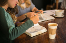 young women at a Bible study reading Bibles and drinking coffee