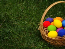 Basket of colored Easter eggs in the grass.
