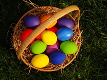 Multicolored Easter eggs in a basket, in the grass.