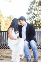 portrait of a bride and groom sitting on a bench outdoors