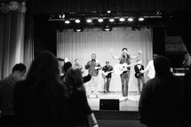 performers on stage singing and praising god